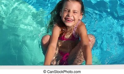 Little girl hold by pool edge and swim in pool with smile