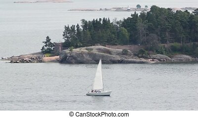 Yacht sail beside rocky coast with beacon and forest at day...