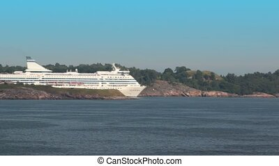 Huge cruiser floats beside coast near Helsinki with forest...