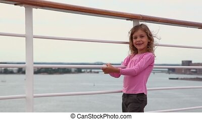 Little girl stands on deck of ship during departure from...