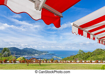Awning over bright sunny blue sky with bench and sea view