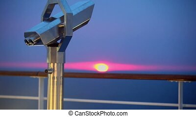 Telescope in shell near fence on deck of ship - Telescope in...