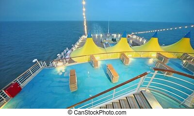Sunbeds near pool and tents on deck of ship which float in sea