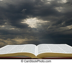 Light on the Bible - Bible open with dark sky in the...