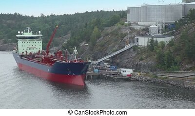 Moorage with industrial ship fills fuel from huge storage...