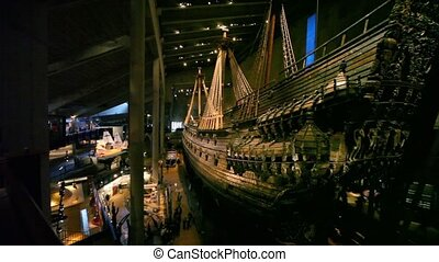 Stern of old tall ship and tourists walk on Vasa Museum