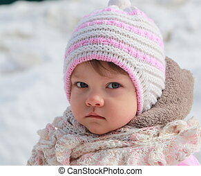 Portrait of baby girl in hat on snow winter background...