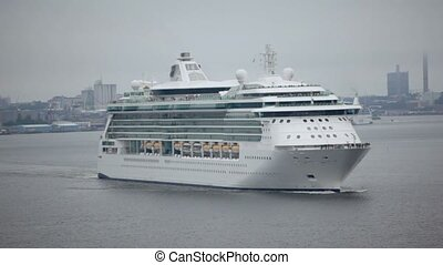 Huge passengers liners float from port near coastal city...