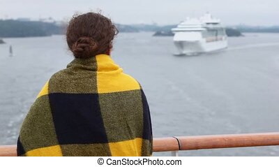 Woman wrapped in plaid stand at deck and watches on cruiser...