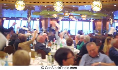 Many people sit at tables and wave shawls in restaurant on ship