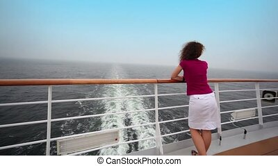 Woman stands on deck near fence and admire seascape during...