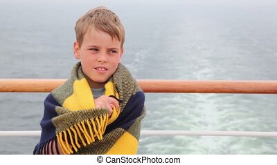 Little boy wrapped in rug stands on deck during cruise