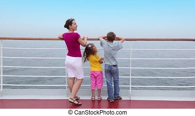 Mother with kids stand on deck near fence and admire seascape
