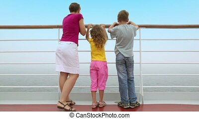Mother with kids stand on deck and watch seascape during...