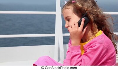 Little girl sits and talks by cell phone on deck near fence...