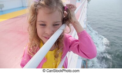 Little girl holds fence at ship edge and admires seascape...