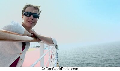 Woman stands near fence on ship and admires seascape - Woman...