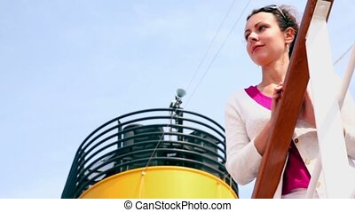 Woman in white jacket stands at fence near tube of ship...