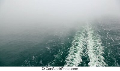 Smoke above froth trace on water surface after ship