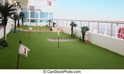 field for mini golf on deck of ship which float on wavy sea