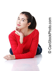 Young beautiful woman in casual clothes lying on floor,...