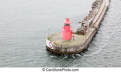 small beacon standing on platform in middle of water, flowed...