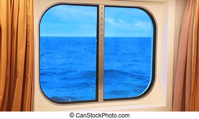 window in ship cabin with dark blue ocean, cloud and sky