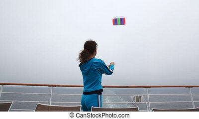 woman flies multi-colored kite in gray sky from ship deck