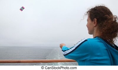 woman by ship deck holds rope from kite in gray sky