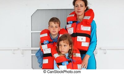mother with son and daughter in life jackets stands on ship...