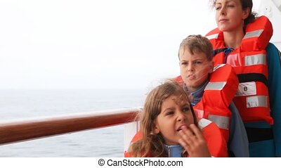mother with son and daughter wave hands from ship deck