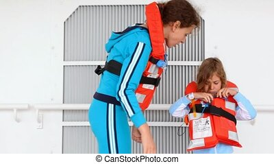 mother helps daughter to fasten rope of life jacket on ship deck