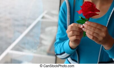 woman is by window ship and holds rose from color paper