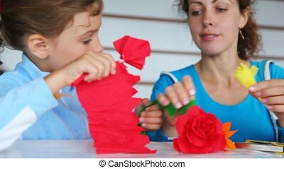 mother with daughter make of color paper flower at table
