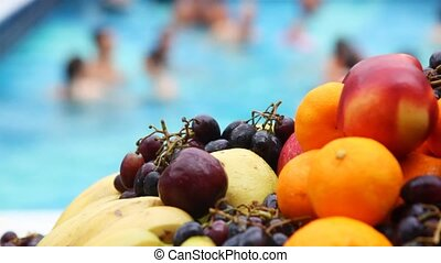 oranges, apples, bananas, grapes close up in front of pool...