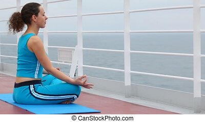 woman in pose of lotus sits on ship deck, having closed eyes