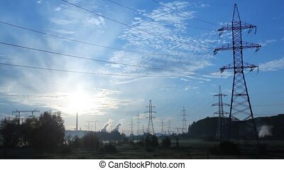 Power transmission lines poles stand against pipes of plant and blue sky