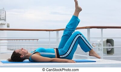 woman in blue lies on back and moves feet in air on ship...