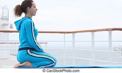 woman in dark blue sits on lap motionlessly on rug on ship deck