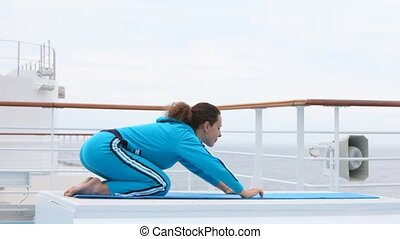 on ship deck woman on rug does physical exercises laying down