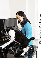 Mature woman and her cat side by side at the piano -...