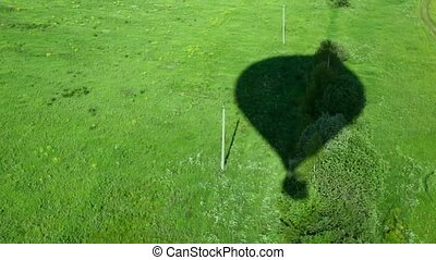 Shadow falls on green grass from flying high balloon