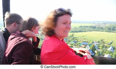 Nice woman flies and smiles in balloon over field and houses