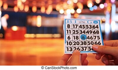 game card bingo in hands close up on dim background of game...
