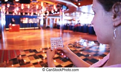 woman holds ticket for game in bingo and looks at leader