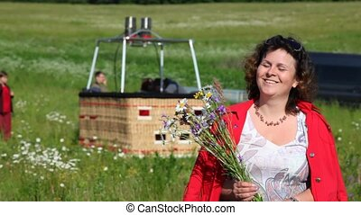 woman stands in front of basket of balloon and holds bouquet...