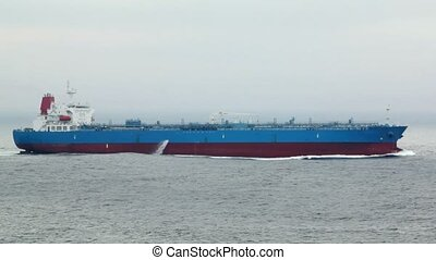 big cargo ship floats on waves in sea at cloudy weather