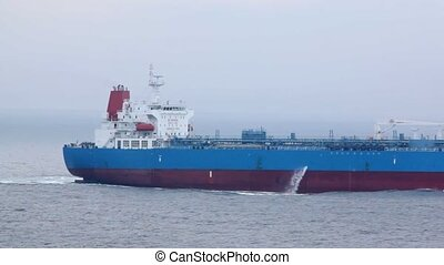 back part of tanker floating on waves in cloudy weather