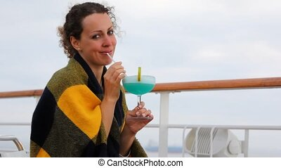 woman wrapped in plaid sits on ship deck with cocktail -...