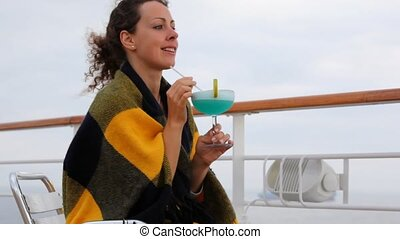 woman under plaid with cocktail glass in hands sits on ship deck